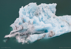 Ice falling off a floating iceberg in Jökulsárlón glacier lagoon in Iceland. Aerial photo captured with a camera drone (Phantom) by Paul Oostveen.