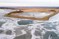 Bevroren Markermeer met achter de dijk natuurgebied De Nek. Luchtfoto gemaakt met een drone.